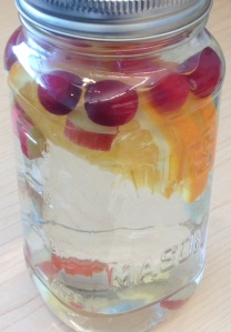 closed mason jar with orange and cranberries floating in water