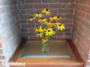 yellow flowers on wooden shelf