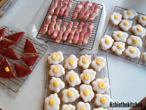 bacon and egg shaped and iced cookies on cooling racks