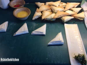 making spanikopeda: folding spinach triangles into fill-pastry