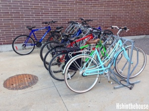 a full bike rack in front of a brick wall