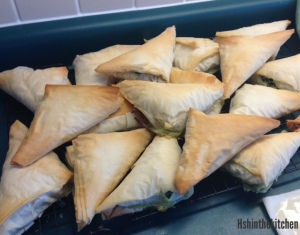 triangular spinach pies on cooling rack