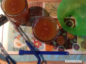 filling jars with peach preserves