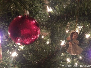 pink bauble and angle ornament on lit christmas boughs